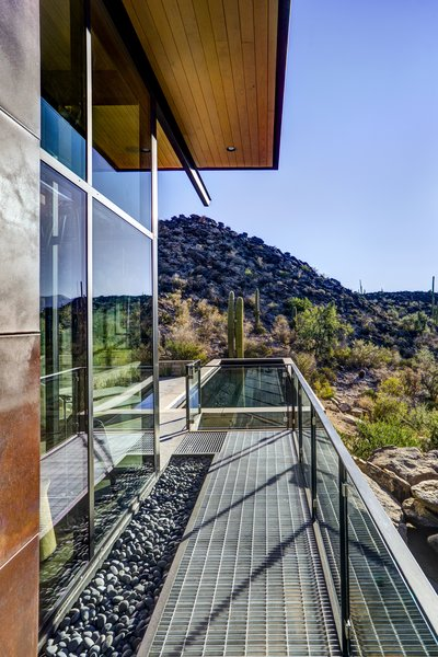 Modern home with outdoor, side yard, desert, lap pool, swimming pool, small pool, small patio, porch, deck, concrete pool, metal patio, porch, deck, and metal fence. Photo 3 of Canyon Pass Home at Dove Mountain