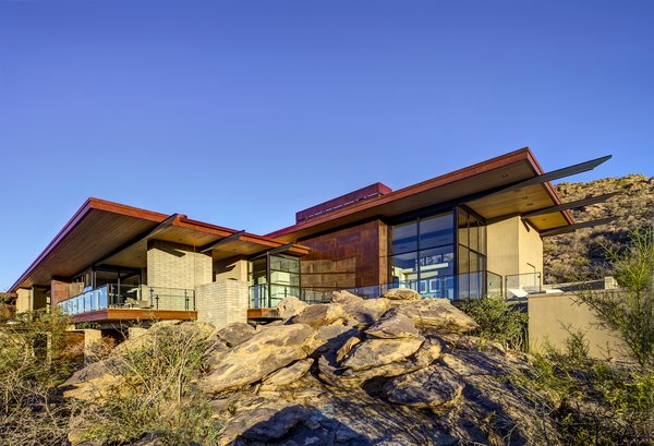 Modern home with outdoor, front yard, side yard, desert, boulders, small patio, porch, deck, metal patio, porch, deck, and metal fence. Photo 4 of Canyon Pass Home at Dove Mountain
