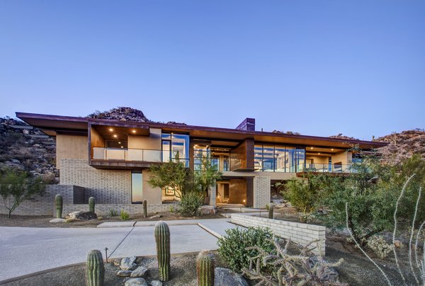 Modern home with outdoor, front yard, desert, boulders, hardscapes, walkways, small patio, porch, deck, concrete patio, porch, deck, and metal fence. Photo 5 of Canyon Pass Home at Dove Mountain