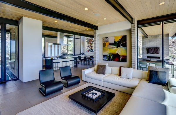 Modern home with living room, chair, sofa, coffee tables, sectional, ceiling lighting, recessed lighting, accent lighting, concrete floor, and ceramic tile floor. Photo 6 of Canyon Pass Home at Dove Mountain