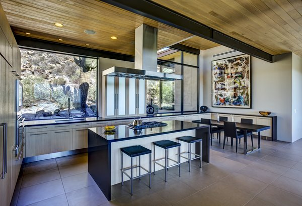 Modern home with kitchen, stone counter, porcelain tile floor, wood cabinet, ceiling lighting, accent lighting, cooktops, wall oven, recessed lighting, refrigerator, range, range hood, undermount sink, and microwave. Photo 7 of Canyon Pass Home at Dove Mountain