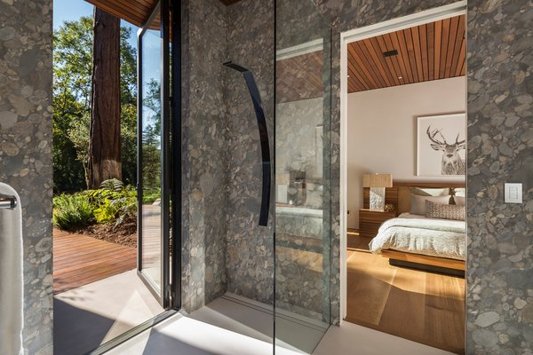 Modern home with bath room and stone counter. Guest bathroom with ancient riverbed stone walls. This doubles as a pool changing room. Photo 17 of Woodside Way