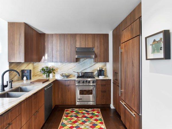 Modern home with kitchen, stone counter, wood cabinet, medium hardwood floor, stone slab backsplashe, range hood, refrigerator, range, dishwasher, and drop in sink. Photo 6 of Castle of Color