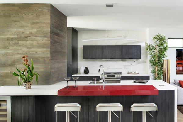 Modern home with kitchen, engineered quartz counter, laminate cabinet, medium hardwood floor, stone slab backsplashe, undermount sink, pendant lighting, and range. Kitchen Photo 2 of Sanders