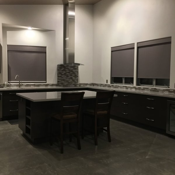 Modern home with kitchen, wood cabinet, engineered quartz counter, ceramic tile backsplashe, concrete floor, track lighting, accent lighting, and drop in sink. Kitchen, a clean look with no upper cabinets and a lot of light was the intent of the design. Photo 2 of 2017 Norton Jones