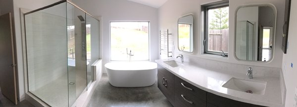 Modern home with bath room, freestanding tub, concrete floor, open shower, recessed lighting, drop in sink, engineered quartz counter, and stone tile wall. Master Bath Photo  of 2017 Norton Jones