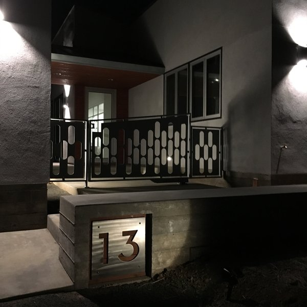 Modern home with outdoor, front yard, metal fence, and landscape lighting. Front Entry, luck number 13 and a custom made pivot gate. Photo 4 of 2017 Norton Jones