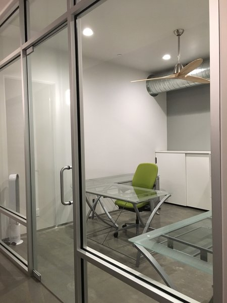 Modern home with office, chair, and concrete floor. Office, store front glass wall to let the outside light in from the adjacent slider in the hallway. This room has no external wall / window and was a great idea from the builder. Photo 3 of 2017 Norton Jones