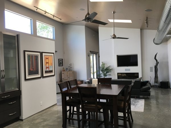 Modern home with living room, sofa, track lighting, concrete floor, and ribbon fireplace. Living / Dining  Photo 8 of 2017 Norton Jones