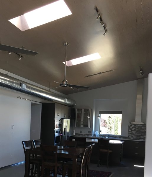 Modern home with kitchen, wood cabinet, engineered quartz counter, concrete floor, metal cabinet, ceramic tile backsplashe, track lighting, pendant lighting, refrigerator, microwave, wall oven, and drop in sink. Kitchen / Dining. illustrating the airy and open  main living area. Photo 5 of 2017 Norton Jones