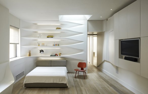 Modern home with bedroom, bookcase, bed, shelves, wall lighting, recessed lighting, and medium hardwood floor. View towards the bedroom Photo  of K Residence
