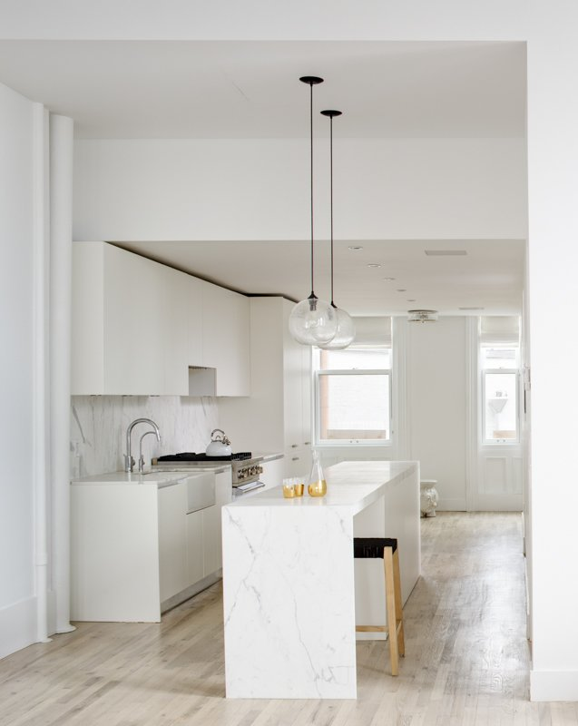 Kitchen Tagged: Kitchen, Marble Counter, Light Hardwood Floor, White Cabinet, Stone Tile Backsplashe, Pendant Lighting, Recessed Lighting, and Drop In Sink.  Grand St. Residence by SU11 Architecture+Design