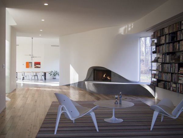 Modern home with living room, chair, medium hardwood floor, recessed lighting, and wood burning fireplace. Interior View of Fireplace Photo 3 of DR Residence