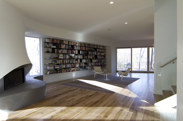 Modern home with living room, bench, wood burning fireplace, medium hardwood floor, ceiling lighting, and recessed lighting. View of Fireplace and Library Photo 4 of DR Residence