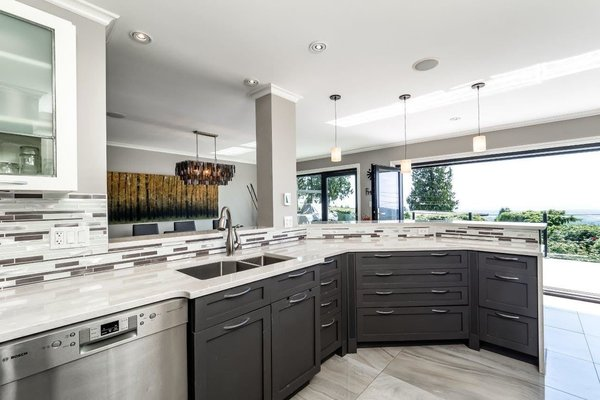 Modern home with kitchen, ceiling lighting, table lighting, travertine floor, stone counter, refrigerator, pendant lighting, dishwasher, range, and range hood. Photo  of City and Ocean View Home