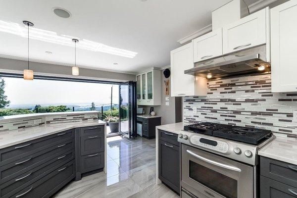 Modern home with kitchen, travertine floor, glass tile backsplashe, stone counter, ceiling lighting, pendant lighting, and range. Photo 2 of City and Ocean View Home