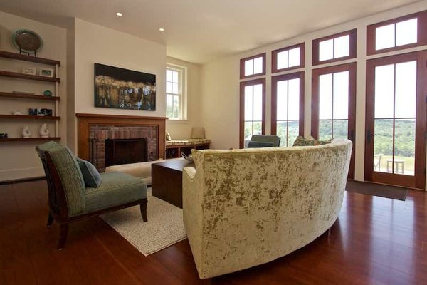 Modern home with living room, bench, sofa, end tables, chair, coffee tables, ceiling lighting, floor lighting, wood burning fireplace, and medium hardwood floor. Additional Living Room with Fireplace Built ins and Views Photo 7 of Dennis Wedlick Design Spencertown Home