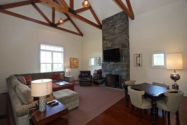 Modern home with living room. Great Room with Beams Stone Fireplace Game Table and Reading Loft Photo 12 of Dennis Wedlick Design Spencertown Home