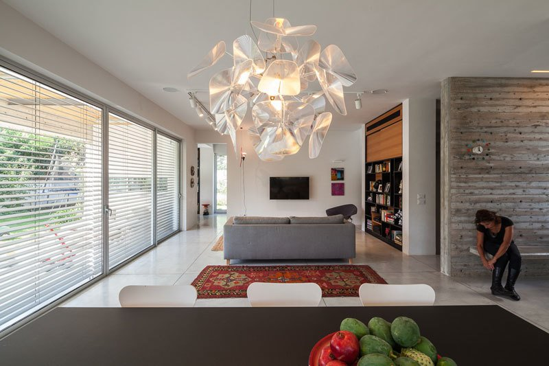 Tagged: Table, Concrete Floor, Table Lighting, Ceiling Lighting, Pendant Lighting, Track Lighting, Living Room, Bench, Sofa, and Carpet Floor.  Urban Life In The Country by Eshet Alperovich Arch