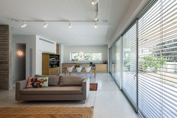 Modern home with living room, sofa, ceiling lighting, track lighting, concrete floor, and carpet floor. Photo 6 of Urban Life In The Country