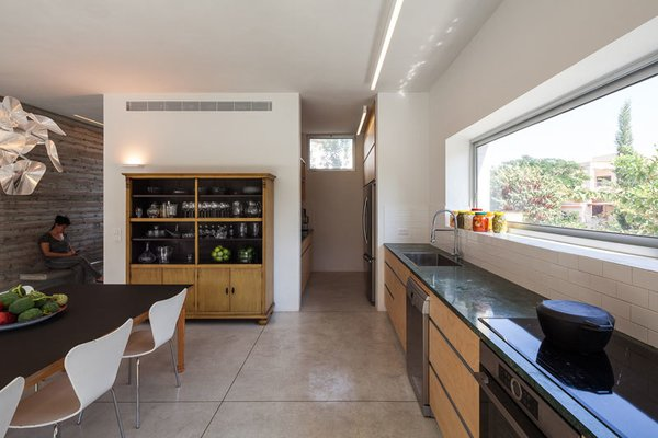 Modern home with kitchen, marble counter, ceramic tile backsplashe, concrete floor, wood cabinet, track lighting, ceiling lighting, pendant lighting, dishwasher, and cooktops. Photo 8 of Urban Life In The Country