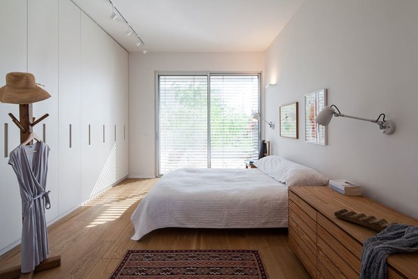Modern home with bedroom, bed, wardrobe, storage, medium hardwood floor, night stands, and wall lighting. Photo 12 of Urban Life In The Country