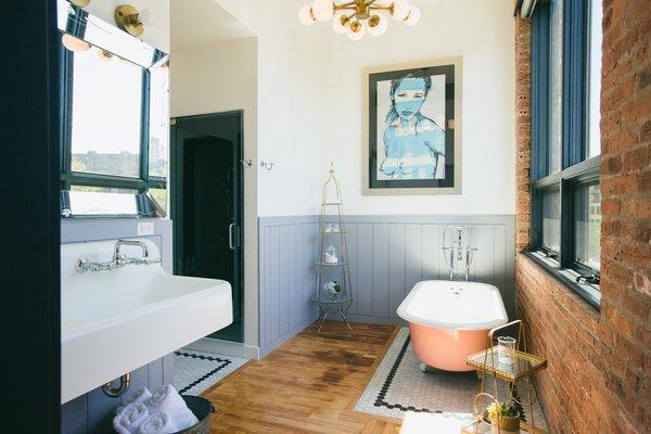 Modern home with bath room, medium hardwood floor, vessel sink, wall mount sink, ceramic tile floor, soaking tub, enclosed shower, ceiling lighting, and freestanding tub. Everleigh Room Photo 4 of The Publishing House Bed & Breakfast