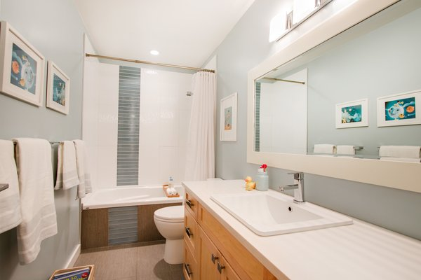 Modern home with bath room, engineered quartz counter, drop in sink, ceiling lighting, soaking tub, and tile counter. Second bathroom  Photo 19 of Bayview Road