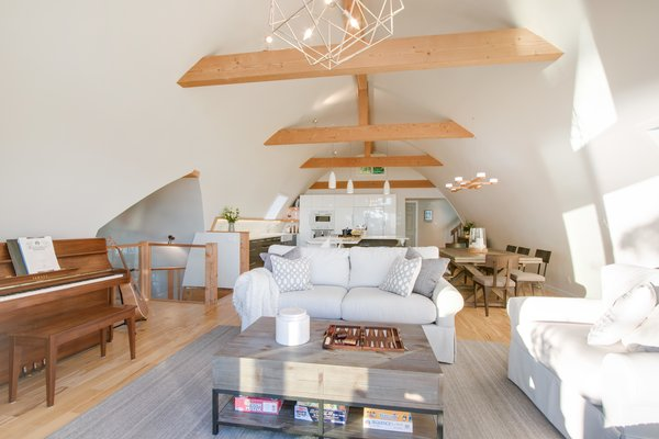 Modern home with living room, sofa, chair, coffee tables, ceiling lighting, and medium hardwood floor. Great room looking to kitchen  Photo 4 of Bayview Road