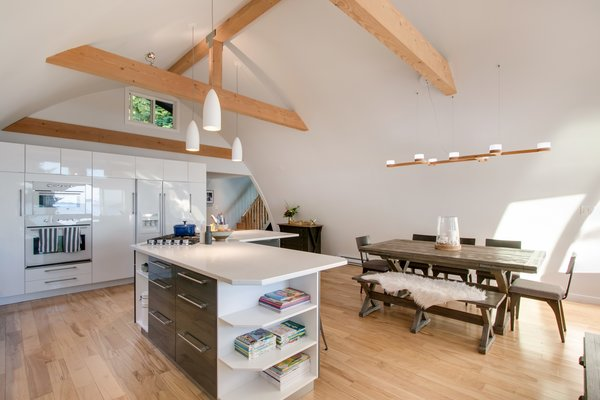 Modern home with dining room, chair, table, bar, bench, storage, stools, ceiling lighting, shelves, and medium hardwood floor. Kitchen and dining rooms  Photo 6 of Bayview Road