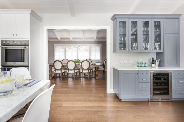 Modern home with kitchen, medium hardwood floor, quartzite counter, colorful cabinet, wine cooler, and wall oven. Custom Built-In Bar incorporated into great room Photo 3 of Danville Transitional Remodel