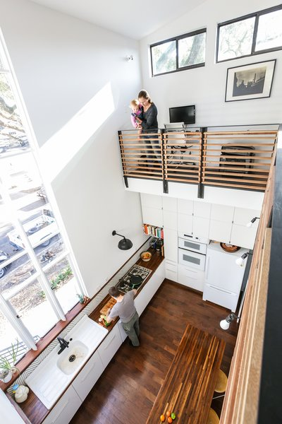 The double height interior space overlooks the kitchen. A large custom operable assembly of windows frames views to the Oak lined street.