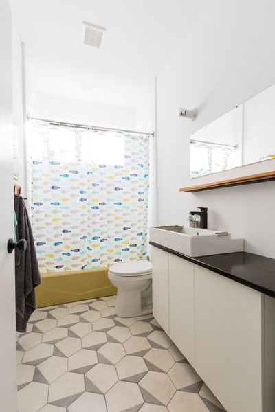 Modern home with bath room, vessel sink, wood counter, drop in tub, ceramic tile floor, and wall lighting. Bathrooms include cement tile by Cle, and salvaged tubs from a local building material re-sale store.  Photo 5 of Dorgenois