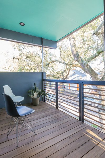 Modern home with outdoor, small patio, porch, deck, front yard, wood patio, porch, deck, trees, and horizontal fence. In addition to the generous side porch, the home includes a more intimate upstairs porch perched in the tree canopy.  Photo 6 of Dorgenois