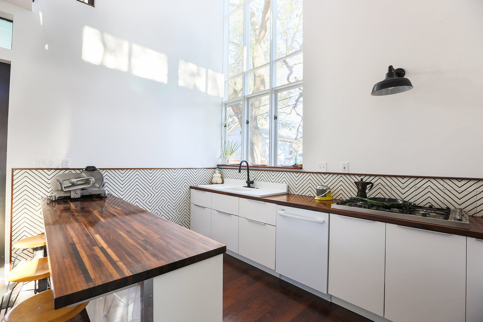 The light-filled kitchen space. Cle tiles are used as backsplash, Ikea cabinets and Walnut butcher-block countertops make the working surfaces of the space.