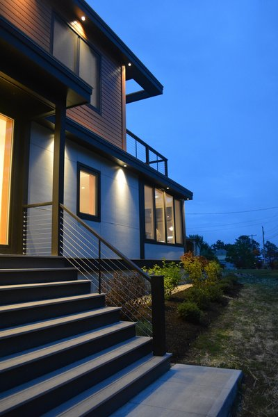 Modern home with outdoor, wood patio, porch, deck, shrubs, wire fence, front yard, and landscape lighting. Entry looking toward beach Photo 2 of Eiderdown