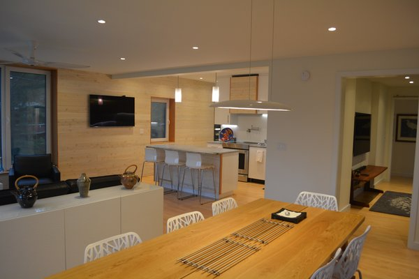 Modern home with white cabinet, recessed lighting, wood cabinet, light hardwood floor, engineered quartz counter, pendant lighting, range, range hood, table, stools, bar, chair, living room, and console tables. Living/Dining looking toward Kitchen Photo 4 of Eiderdown