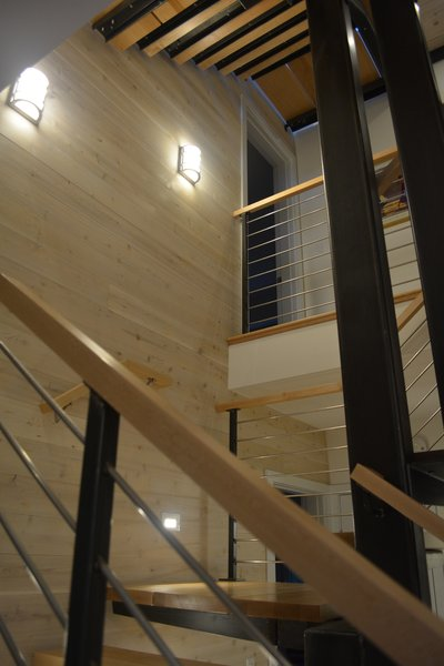 Modern home with staircase, metal tread, wood tread, wood railing, and metal railing. Stair looking up between levels and landings Photo 7 of Eiderdown