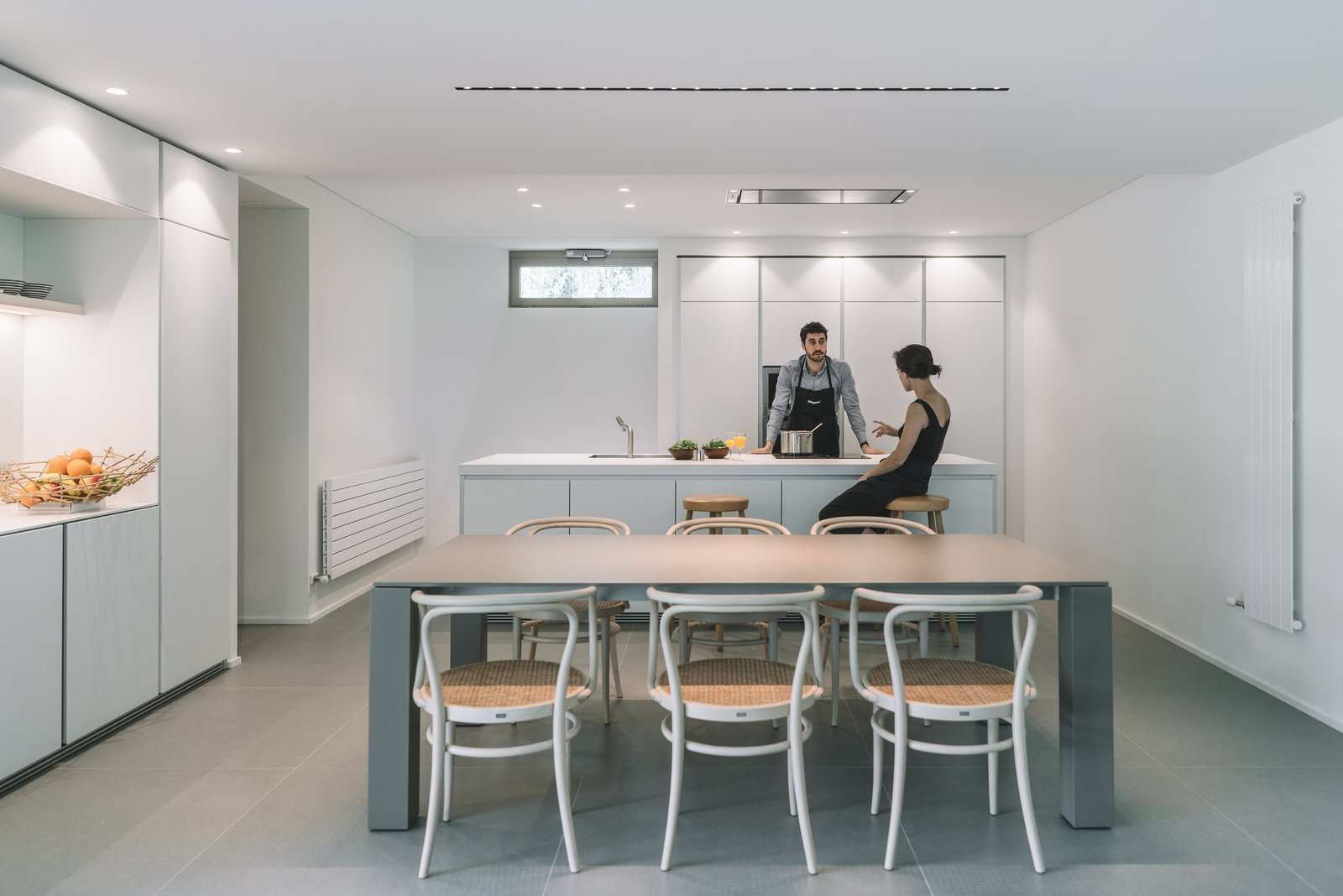 Tagged: Kitchen, Ceiling Lighting, White Cabinet, Porcelain Tile Floor, Laminate Counter, Wall Oven, and Drop In Sink.  The Öcher House by MLMR Architecture Consultancy