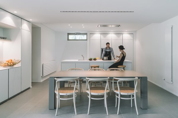 Modern home with kitchen, ceiling lighting, white cabinet, porcelain tile floor, laminate counter, wall oven, and drop in sink. Photo 13 of The Öcher House