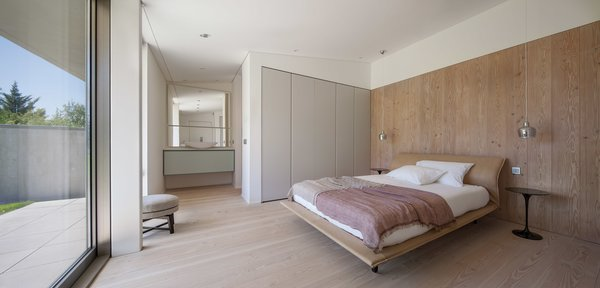 Modern home with bedroom, wardrobe, bed, ceiling lighting, pendant lighting, night stands, and light hardwood floor. Photo 18 of The Öcher House