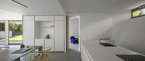 Modern home with laminate counter, porcelain tile floor, ceiling lighting, white cabinet, drop in sink, dining room, table, chair, storage, and shelves. Photo 14 of The Öcher House