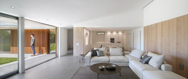 Modern home with laminate counter, white cabinet, ceiling lighting, floor lighting, wall oven, porcelain tile floor, drop in sink, living room, console tables, sofa, and coffee tables. Photo 12 of The Öcher House