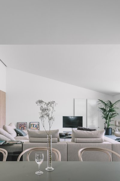 Modern home with sofa, recliner, ottomans, chair, wall lighting, dining room, and table. Photo 15 of The Öcher House