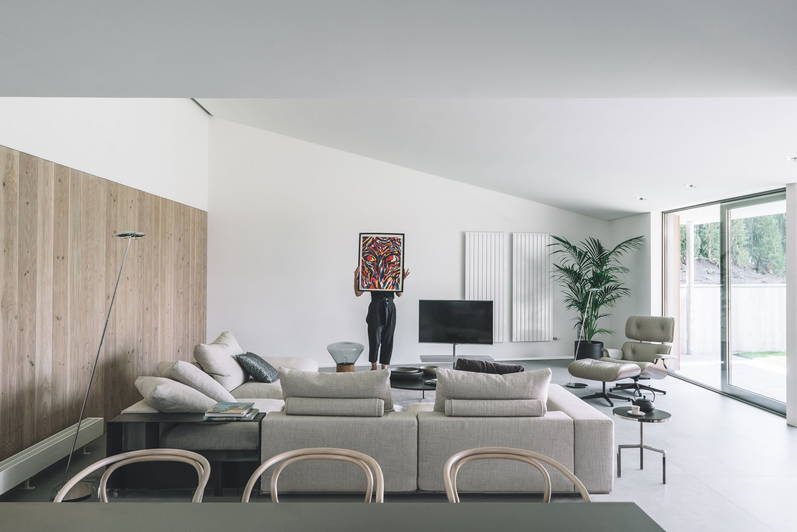 Interior view: Living Room Tagged: Chair, Coffee Tables, Wall Lighting, Ottomans, Sofa, End Tables, Porcelain Tile Floor, and Kitchen. The Öcher House by MLMR Architecture Consultancy
