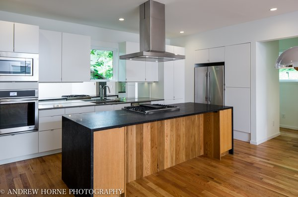 Modern home with kitchen, granite counter, engineered quartz counter, white cabinet, wood cabinet, ceiling lighting, recessed lighting, light hardwood floor, mirror backsplashe, refrigerator, wall oven, range, microwave, range hood, undermount sink, and dishwasher. Kitchen Photo 8 of Tree House