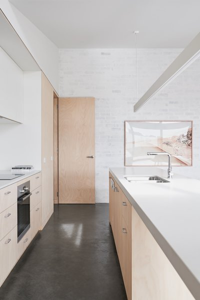 Kitchen featuring custom sustainable joinery by The Nest, recycled brick wall with no VOC paint, and photography by Brooke Holm (represented by Modern Times).