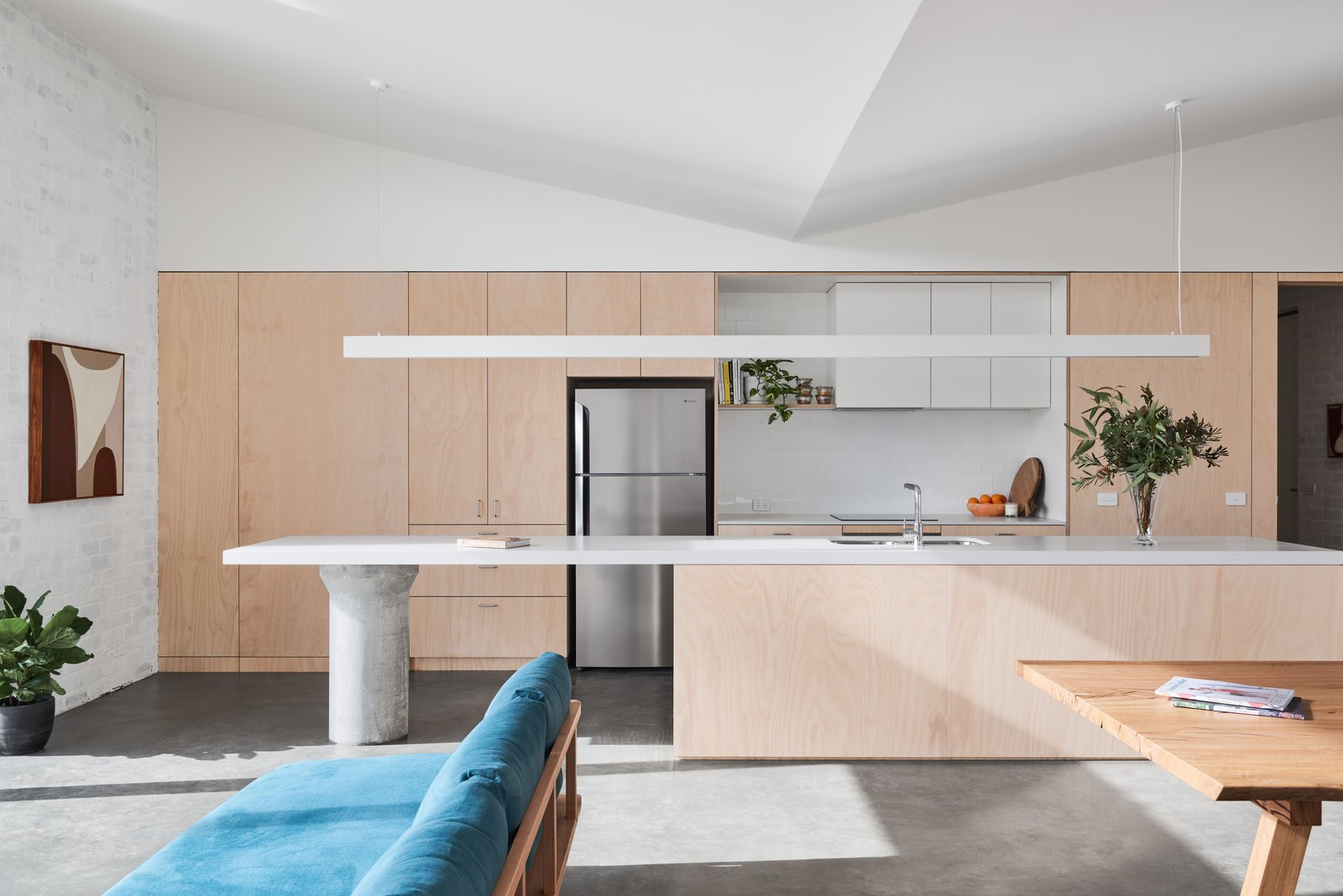 North-facing living/dining for passive solar heating, and butterfly-shaped ceiling for cross-flow ventilation cooling. Australian-made couch by Pop & Scott. Recycled timber dining table by Finding The Grain.