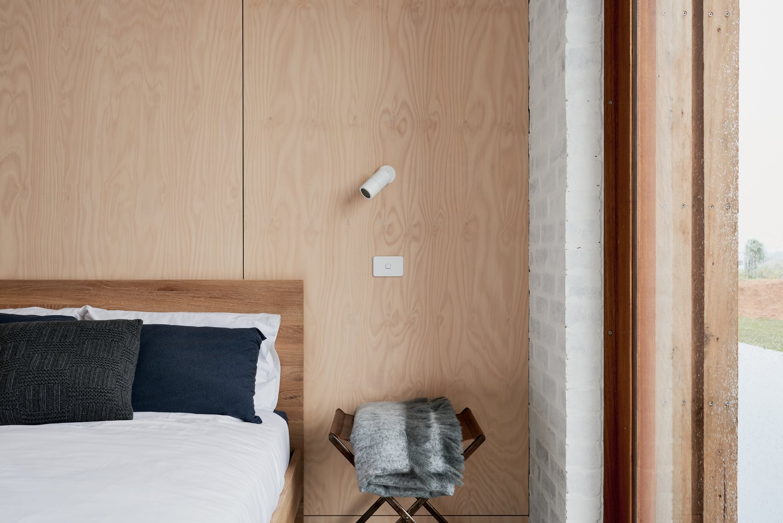 Main bedroom featuring recycled brick walls and sustainable, non-toxic plywood panelling. Sustainable timber bed by Totem Road. Tagged: Bedroom, Bed, Chair, Ceiling Lighting, Night Stands, Wall Lighting, Accent Lighting, and Concrete Floor.  The 10 Star Home by The Sociable Weaver