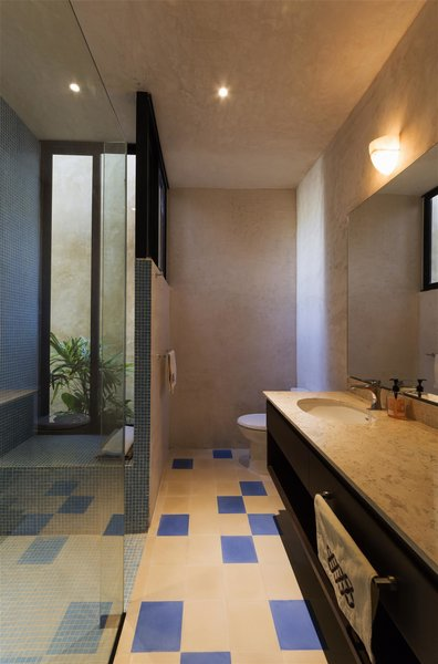 Modern home with bath room, granite counter, ceramic tile floor, drop in sink, enclosed shower, concrete wall, ceiling lighting, and stone tile wall. Photo 6 of Casa RC80
